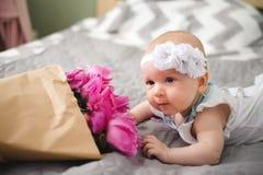 Nyfött behandla som ett barn att lägga på baden med blommabuketten Arkivbild