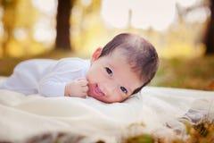 Nyfött behandla som ett barn att lägga på gräset Royaltyfri Foto