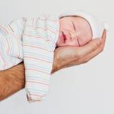 Nyfött behandla som ett barn att le i hans sömn Arkivfoto