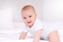 Nyfött behandla som ett barn att le och att se kameran Arkivbild