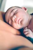 Nyfött behandla som ett barn att sova fridfullt över modern Royaltyfria Bilder