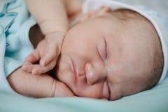 Nyfött behandla som ett barn att sova hemma close upp Arkivfoton