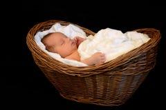Nyfött behandla som ett barn att sova i en träkorg Royaltyfria Bilder