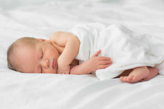 Nyfött behandla som ett barn att sova på en filt Arkivfoto