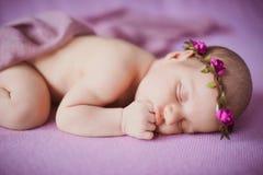 Nyfött behandla som ett barn att sova på en rosa bakgrund Royaltyfri Fotografi