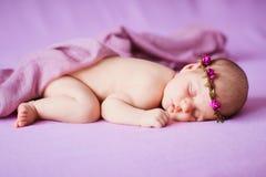 Nyfött behandla som ett barn att sova på en rosa bakgrund Fotografering för Bildbyråer