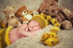 Nyfött behandla som ett barn att sova på leksakbakgrund Arkivfoto