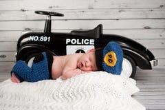 Nyfött behandla som ett barn bära en polisdräkt Arkivbilder