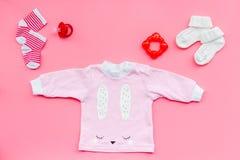 Nyfött behandla som ett barn bakgrund för ` s Kläder för liten flicka med byten på bästa sikt för rosa bakgrund Royaltyfria Bilder