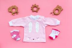 Nyfött behandla som ett barn bakgrund för ` s Kläder för liten flicka med byten på bästa sikt för rosa bakgrund Arkivfoton
