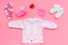 Nyfött behandla som ett barn bakgrund för ` s Kläder för liten flicka med byten på bästa sikt för rosa bakgrund Royaltyfri Foto