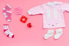 Nyfött behandla som ett barn bakgrund för ` s Kläder för liten flicka med byten på bästa sikt för rosa bakgrund Fotografering för Bildbyråer
