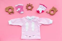 Nyfött behandla som ett barn bakgrund för ` s Kläder för liten flicka med byten på bästa sikt för rosa bakgrund Arkivbild