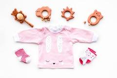 Nyfött behandla som ett barn bakgrund för ` s Kläder för liten flicka med byten på den vita bästa sikten Royaltyfri Foto