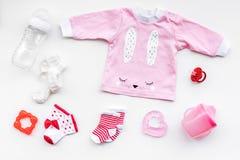 Nyfött behandla som ett barn bakgrund för ` s Kläder för liten flicka med byten på den vita bästa sikten Royaltyfria Foton