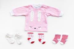 Nyfött behandla som ett barn bakgrund för ` s Kläder för liten flicka med byten på den vita bästa sikten Fotografering för Bildbyråer