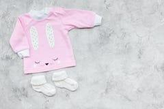 Nyfött behandla som ett barn bakgrund för ` s Kläder för liten flicka med byten på grått utrymme för kopia för bästa sikt för bak Royaltyfria Bilder