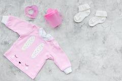 Nyfött behandla som ett barn bakgrund för ` s Kläder för liten flicka med byten på grått utrymme för kopia för bästa sikt för bak Arkivfoton