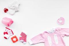 Nyfött behandla som ett barn bakgrund för ` s Kläder för liten flicka med byten på vitt kopieringsutrymme för bästa sikt Royaltyfria Bilder