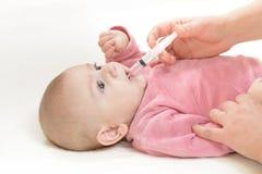 Nyfött behandla som ett barn får medicin royaltyfria foton