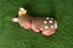 Nyfött behandla som ett barn flickan lismar in/hjortdräkten Fotografering för Bildbyråer