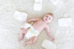 Nyfött behandla som ett barn flickan med blöjor Torr hud och barnkammare Arkivbild