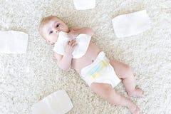 Nyfött behandla som ett barn flickan med blöjor Torr hud och barnkammare Arkivfoto