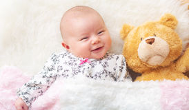 Nyfött behandla som ett barn flickan på hennes filt med hennes nallebjörn Arkivbilder