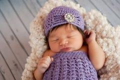 Nyfött behandla som ett barn flickan som bär en klaffhatt Arkivfoton