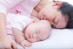 Nyfött behandla som ett barn flickan som sover i moderarm Arkivbild