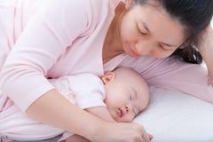 Nyfött behandla som ett barn flickan som sover i moderarm Arkivfoton
