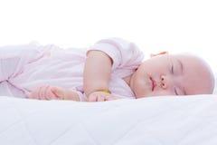 Nyfött behandla som ett barn flickan som sover i säng Arkivfoto