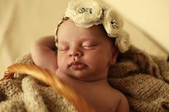 Nyfött behandla som ett barn flickan som sover under den hemtrevliga filten i korg Arkivbild