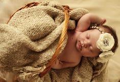 Nyfött behandla som ett barn flickan som sover under den hemtrevliga filten i korg Fotografering för Bildbyråer