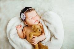 Nyfött behandla som ett barn flickasömnar som slås in i den vita filten Arkivbild
