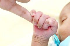 Nyfött behandla som ett barn gripa moderfingret arkivbilder
