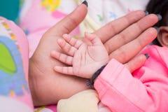 Nyfött behandla som ett barn handen i Mother& x27; s-hand Royaltyfria Foton