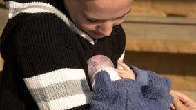 Nyfött behandla som ett barn hjälp med hennes handmoder med flaskan med formel arkivbilder