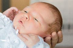 Nyfött behandla som ett barn i armarna av mamman, farsa Stora händer av modern, fathe Arkivbilder