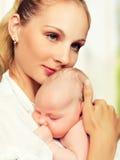 Nyfött behandla som ett barn i armarna av modern Royaltyfri Bild
