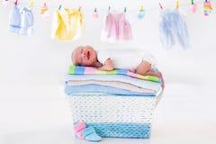 Nyfött behandla som ett barn i en korg med handdukar arkivfoto
