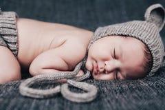 Nyfött behandla som ett barn i en stucken dräkt sovande på en grå pläd Royaltyfri Bild