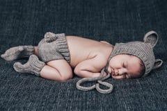 Nyfött behandla som ett barn i en stucken dräkt sovande på en grå pläd Royaltyfria Bilder