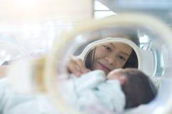 Nyfött behandla som ett barn i kapsel med det älskvärda ögat av modern royaltyfri foto