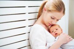 Nyfött behandla som ett barn i mjuk omfamning av modern Arkivfoto