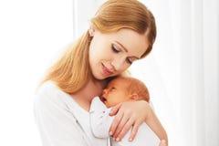 Nyfött behandla som ett barn i mjuk omfamning av modern fotografering för bildbyråer