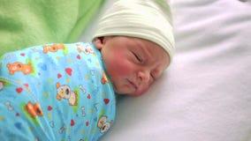 Nyfött behandla som ett barn i sjukhusrum Spädbarn som sover i sängkantbabylift pojke little stock video