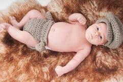 Nyfött behandla som ett barn i stucken blåttkläder Arkivfoto