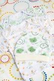 Nyfött behandla som ett barn kläder ställer in: två t-skjortor och stickade plagglitet barnhatt Arkivfoto