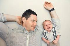 Nyfött behandla som ett barn klätt som gentleman med hans pappa Arkivbild